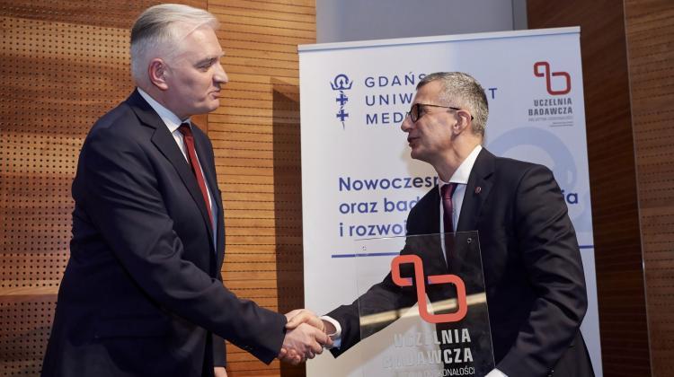 Wicepremier, minister nauki i szkolnictwa wyższego Jarosław Gowin (L) wręcza status